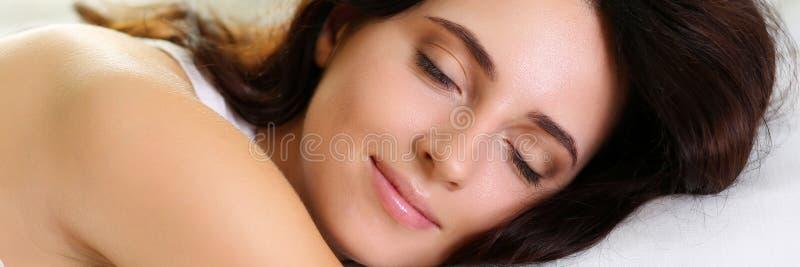 Retrato moreno hermoso joven de la mujer que miente en cama foto de archivo