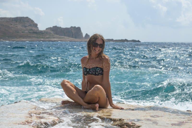 Retrato Mujer joven que se sienta en una roca grande y miradas en la distancia en el mar Foco suave selectivo Días de verano feli fotos de archivo