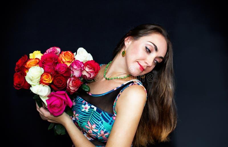 Retrato Mulher feliz, bonita que senta-se com um ramalhete das rosas, em um fundo preto Um presente para a mulher fotografia de stock royalty free