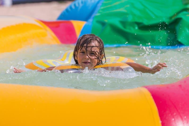 Retrato, nadadas felices de la niña en la piscina imagen de archivo