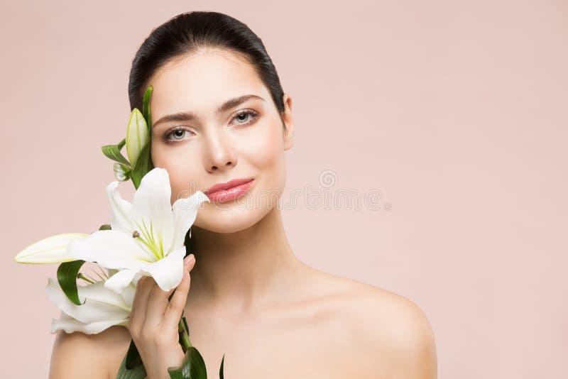 Retrato natural da composição da beleza da mulher com Lily Flower, cuidados com a pele felizes da cara da menina e tratamento imagem de stock royalty free