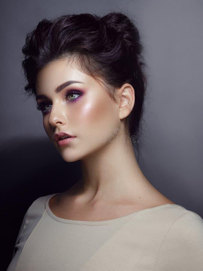 Retrato natural de la belleza de una muchacha con maquillaje perfecto brillante, con el pelo dispuesto, en un fondo gris imagen de archivo libre de regalías