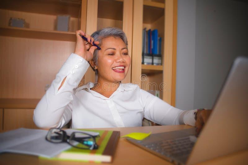 Retrato natural de la oficina de la forma de vida de la mujer asi?tica madura acertada atractiva y feliz que trabaja en la sonris fotografía de archivo libre de regalías