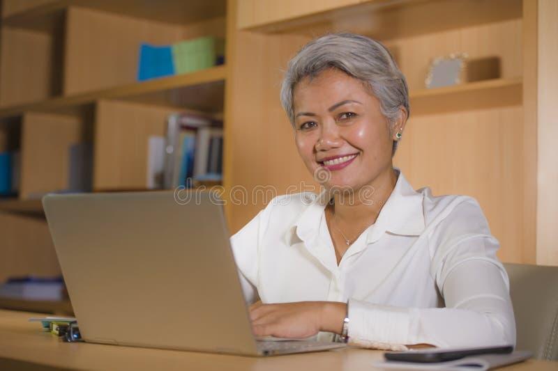 Retrato natural de la oficina de la forma de vida de la mujer asi?tica madura acertada atractiva y feliz que trabaja en la sonris imagen de archivo