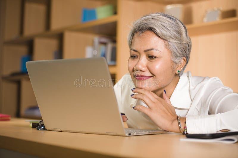 Retrato natural de la oficina de la forma de vida de la mujer asi?tica madura acertada atractiva y feliz que trabaja en la sonris imagenes de archivo