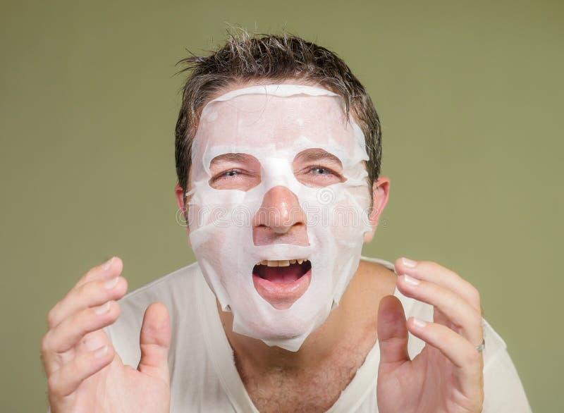 Retrato natural del hombre feliz y divertido joven que aplica la m?scara facial de la belleza que mira en la risa del espejo aleg fotografía de archivo libre de regalías