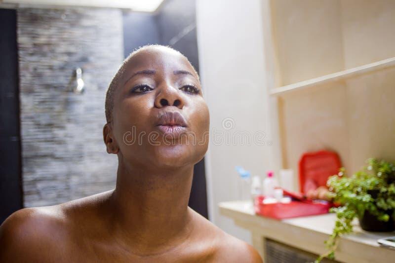 Retrato natural do estilo de vida do banheiro afro-americano preto atrativo e feliz novo da mulher em casa que olha o espelho com fotos de stock