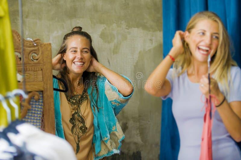 Retrato natural do estilo de vida das amigas bonitas e felizes novas que tentam na compra da roupa alegre na beleza fresca do vin fotografia de stock royalty free