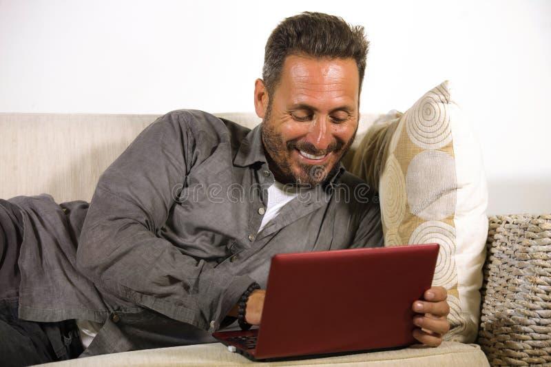 Retrato natural do estilo de vida do homem independente considerável e bem sucedido novo que trabalha em casa usando o encontro d imagens de stock