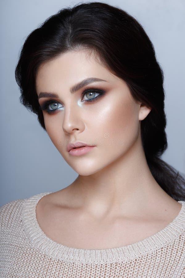 Retrato natural do perfil da beleza de uma menina moreno nova com pele natural no fundo cinzento Tiro vertical do est?dio imagem de stock