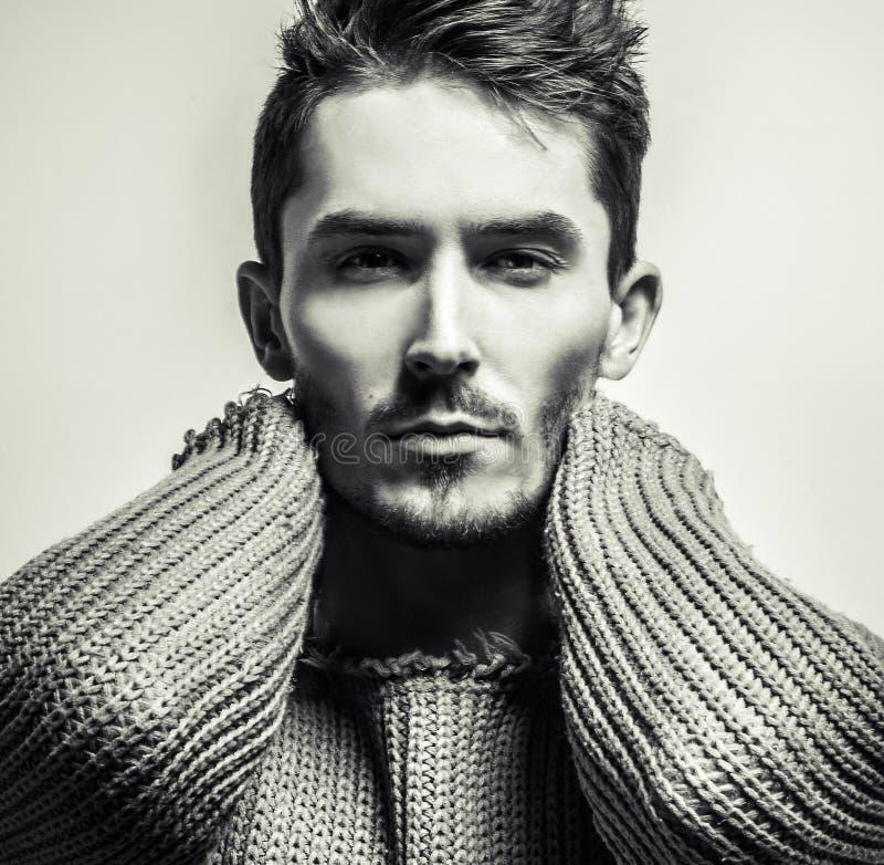 retrato Negro-blanco del estudio del hombre hermoso joven en suéter hecho punto Foto del primer fotografía de archivo