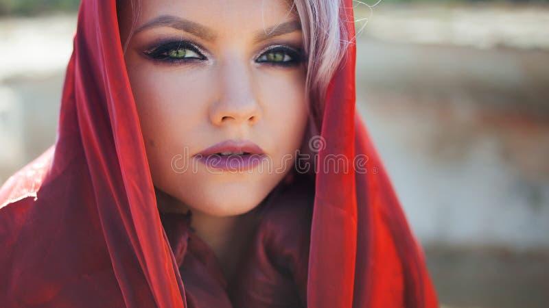 Retrato no estilo oriental Mulher atrativa nova com olhos verdes, um lenço vermelho em sua cabeça foto de stock