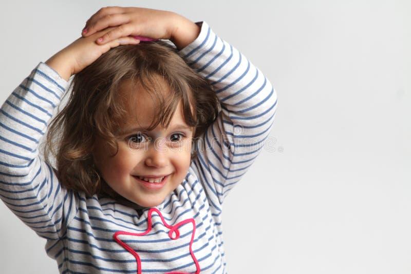 Retrato no fundo branco de uma menina das pessoas de 3-4 anos que joga e que ri imagens de stock