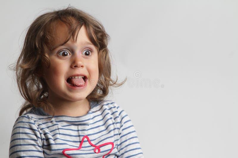 Retrato no fundo branco de uma menina das pessoas de 3-4 anos que joga e que ri imagens de stock royalty free