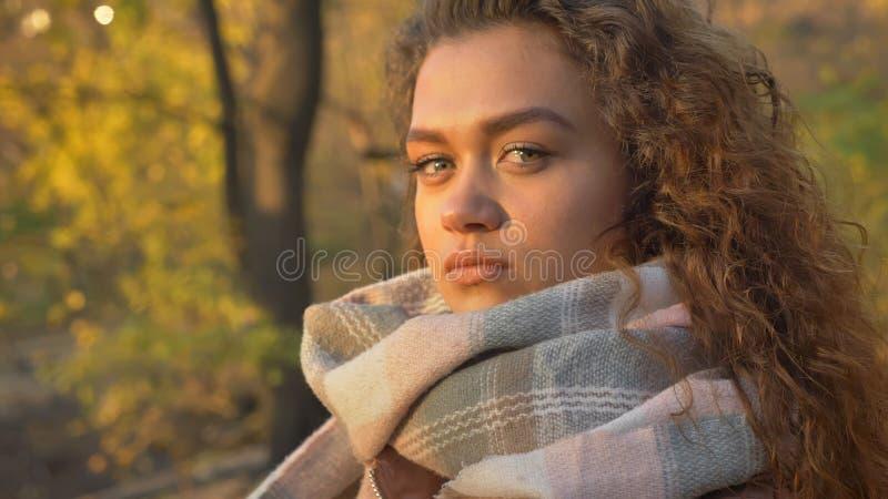 Retrato no perfil da menina caucasiano consideravelmente encaracolado-de cabelo que olha seriamente na câmera no parque outonal fotografia de stock royalty free