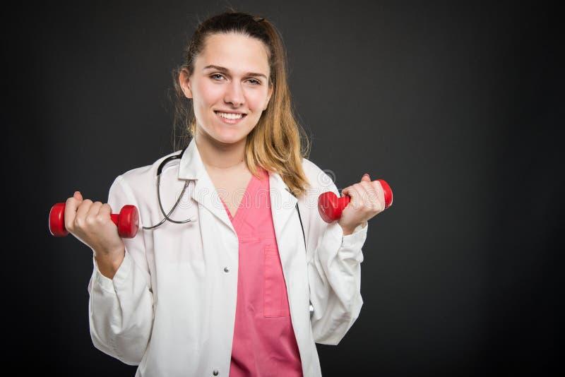 Retrato novo do doutor que guarda pares de pesos que fazem o exercício imagens de stock