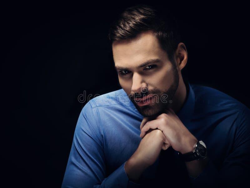Retrato novo do homem de negócios no fundo preto foto de stock royalty free