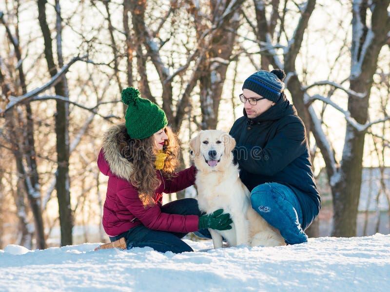 Retrato novo dos pares com o cão no inverno imagens de stock royalty free