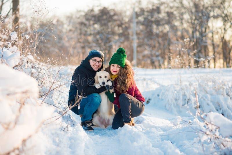 Retrato novo dos pares com o cão no inverno fotografia de stock