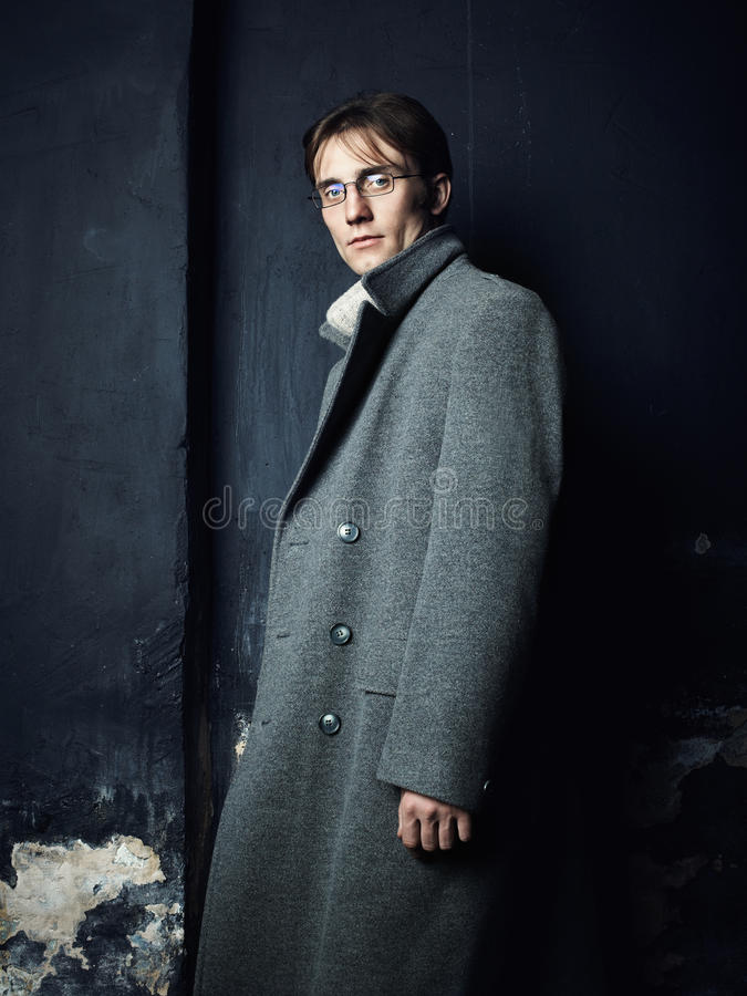 Retrato oscuro artístico del hombre hermoso joven en una capa gris imagenes de archivo
