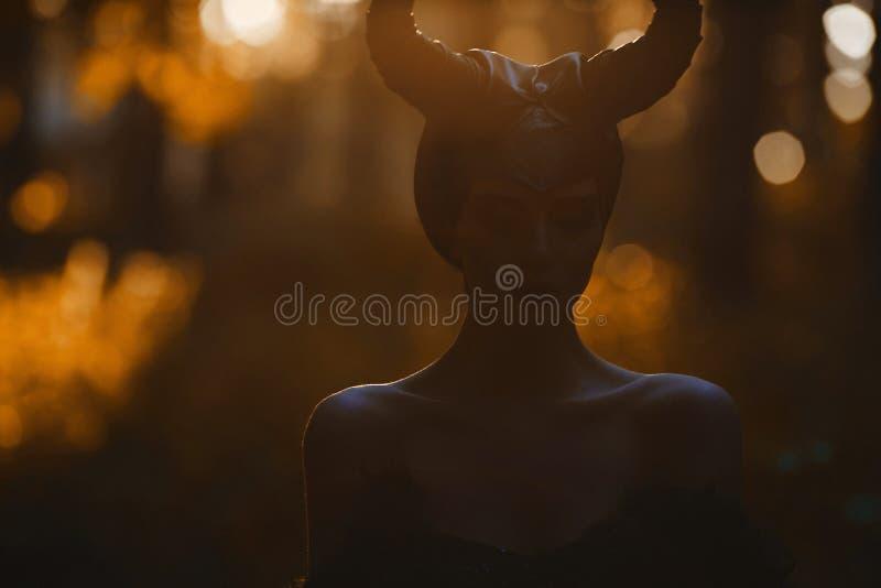 Retrato oscuro de la muchacha modelo morena hermosa y sensual en la imagen de maléfico - historia del cuento de hadas cosplay fotos de archivo