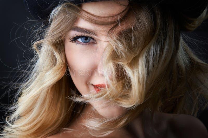 Retrato oscuro de la mujer rubia del encanto, llevando un sombrero, mirando in camera, tiro del estudio, fondo borroso, luz del d fotos de archivo libres de regalías
