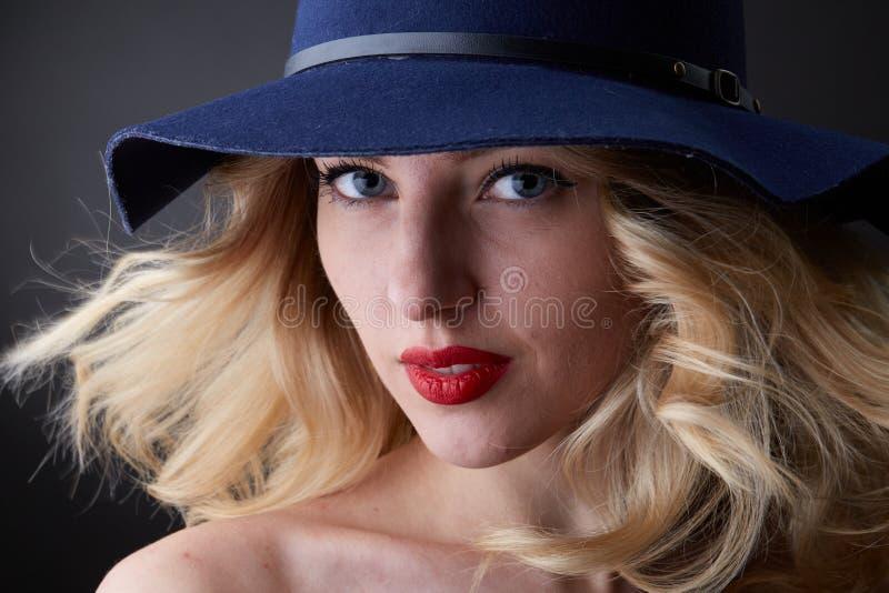 Retrato oscuro de la mujer rubia del encanto, llevando un sombrero, mirando in camera, tiro del estudio, fondo borroso, luz del d fotos de archivo