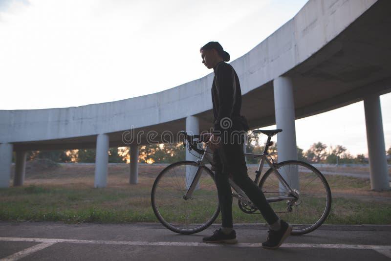 Retrato oscuro de un jinete Silueta de un ciclista con una bicicleta en el fondo de un puente fotografía de archivo libre de regalías