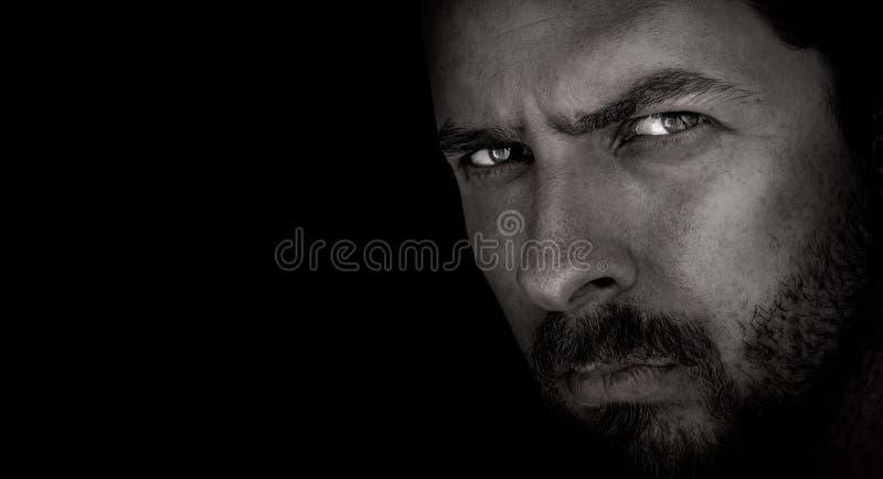 Retrato oscuro del hombre asustadizo con los ojos malvados imagen de archivo