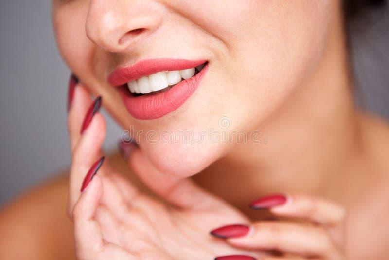Retrato parcial de la mujer que sonríe con la manicura roja y la tez sin defectos foto de archivo