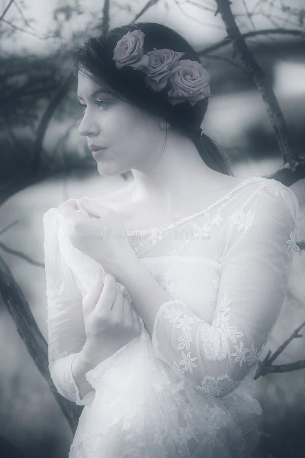 Retrato pensativo joven de la mujer en el vestido y las rosas de encaje blancos en la ha imágenes de archivo libres de regalías
