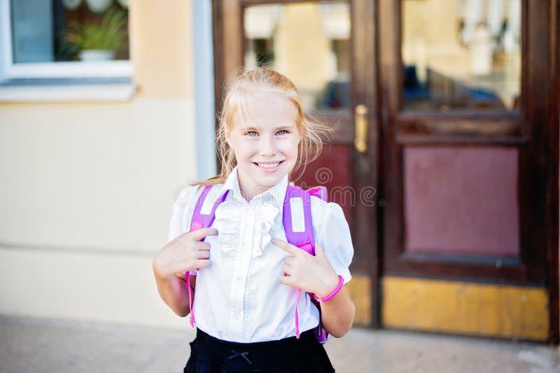 Retrato pequeno feliz da estudante perto da escola fotografia de stock