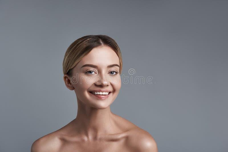Retrato positivo de la mujer feliz sonriente que se opone al fondo gris imagen de archivo libre de regalías