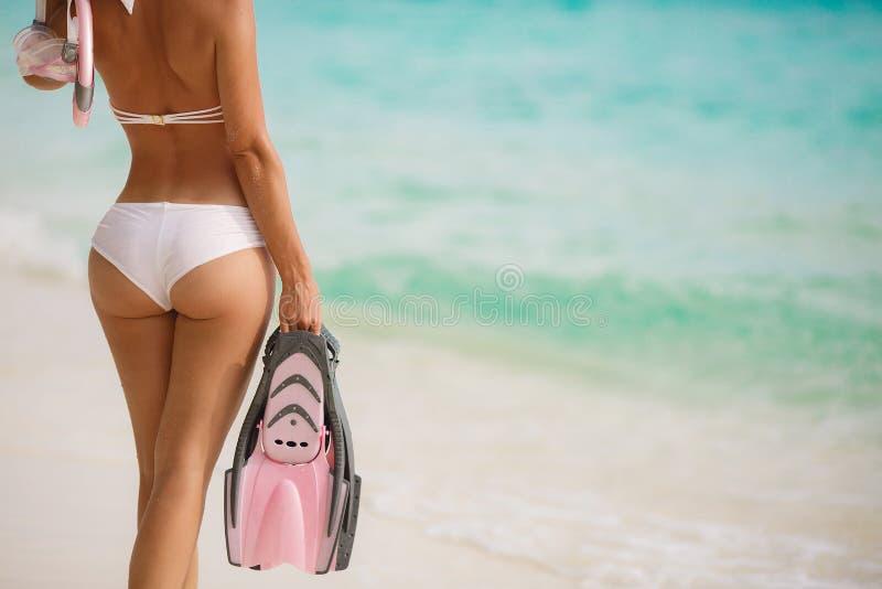Retrato próximo da jovem mulher com pele molhada e com um equipamento mergulhando na areia e ir nadar no oceano claro fotos de stock royalty free