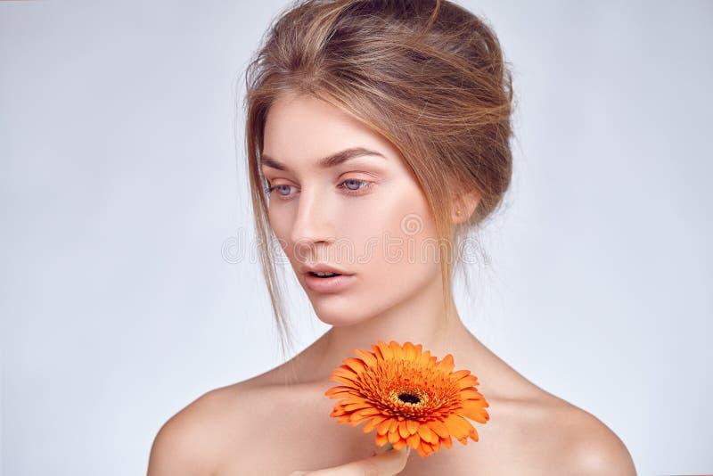 Retrato próximo da moça bonita com flor do gerbera imagens de stock royalty free