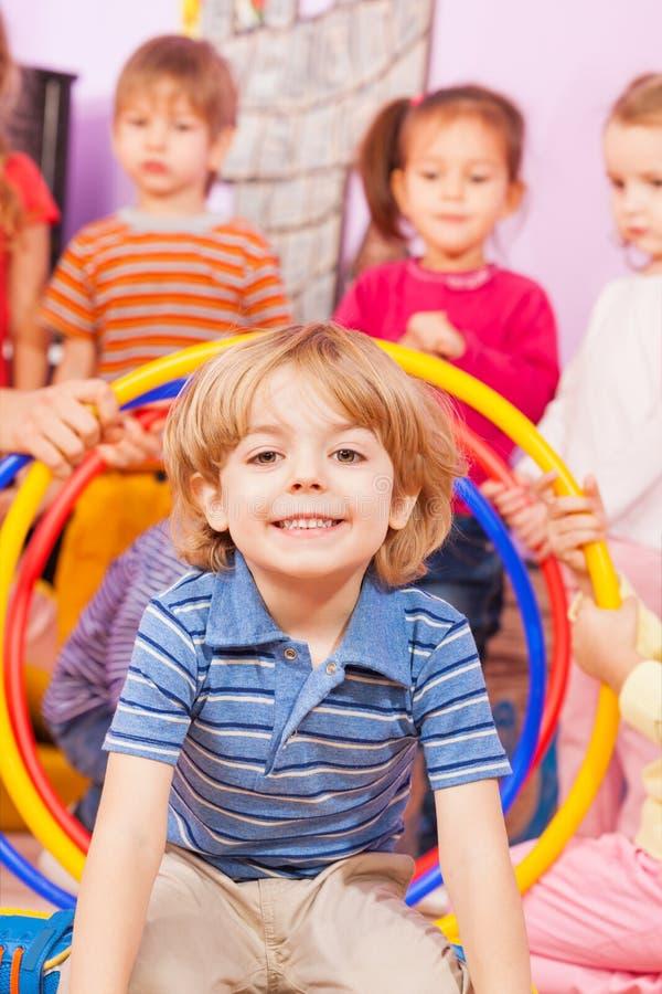Retrato próximo de um menino que joga com outras crianças foto de stock
