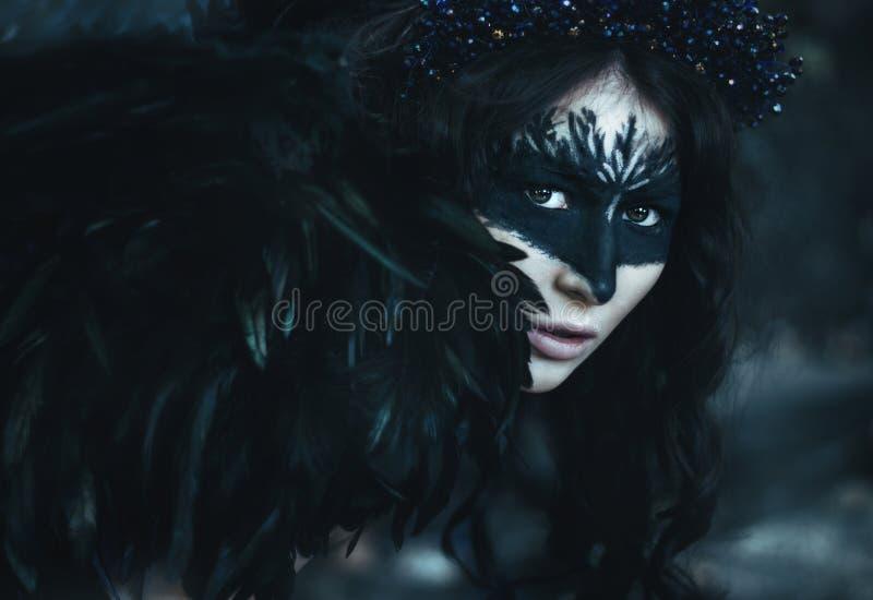 Retrato próximo de uma menina com as asas de um corvo, de um anjo escuro, de uns pássaros e de uma cara do razresovannym fotos de stock