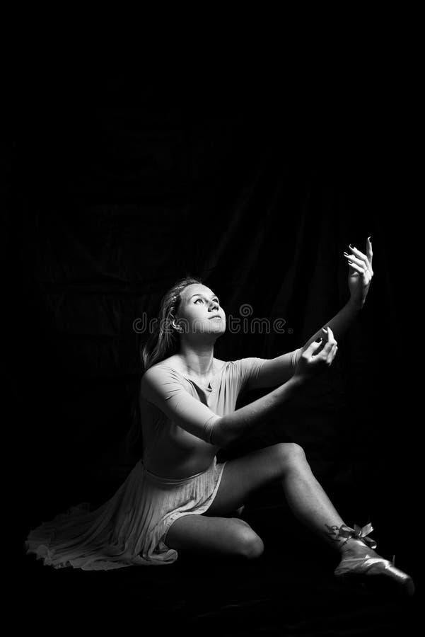 Retrato preto e branco da fotografia da jovem mulher bonita na dança que senta-se no espaço escuro da cópia do fundo foto de stock royalty free