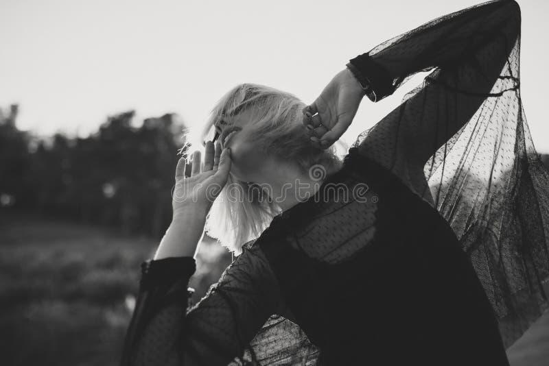 Retrato preto e branco da jovem mulher com cabelo louro e óculos de sol fora na natureza ao dançar imagens de stock