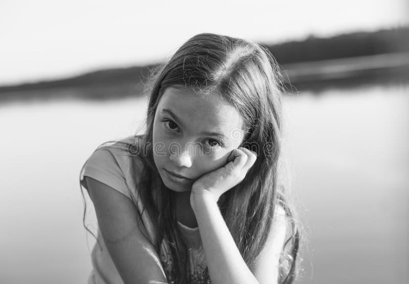 Retrato preto e branco da menina adolescente bonita triste que olha com a cara séria no beira-mar durante o por do sol fotografia de stock