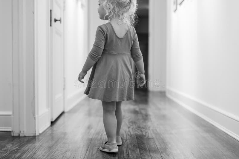 Retrato preto e branco da moça que anda abaixo de um corredor fotos de stock