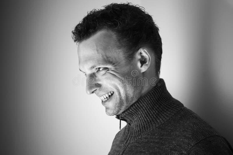 Retrato preto e branco de riso irritado do homem novo imagem de stock