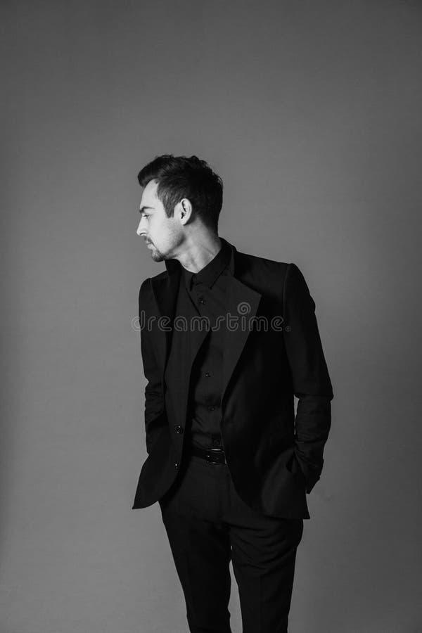 Retrato preto e branco de um homem considerável novo em um terno, posição, mãos em uns bolsos fotos de stock