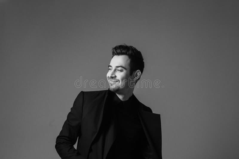 Retrato preto e branco de um homem considerável novo soberbo em um terno fotografia de stock