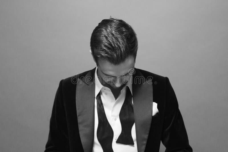 Retrato preto e branco de um homem nos botões de um terno, do laço e de camisa desabotoados imagens de stock