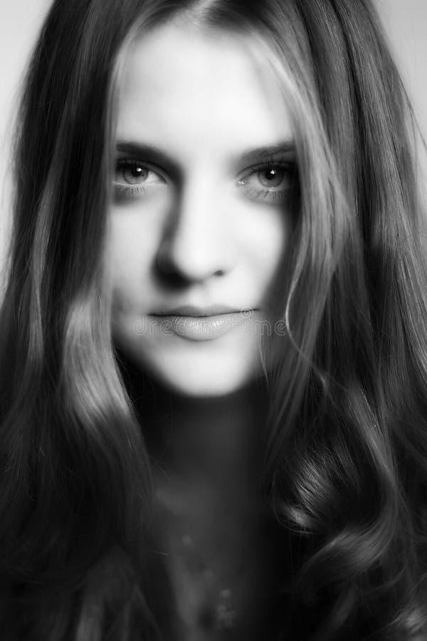 Retrato preto e branco de uma menina de sorriso atrativa nova foto de stock