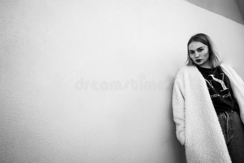 Retrato preto e branco de uma mulher à moda que levanta contra um fundo cinzento ao encontrar-se contra a parede fotos de stock royalty free