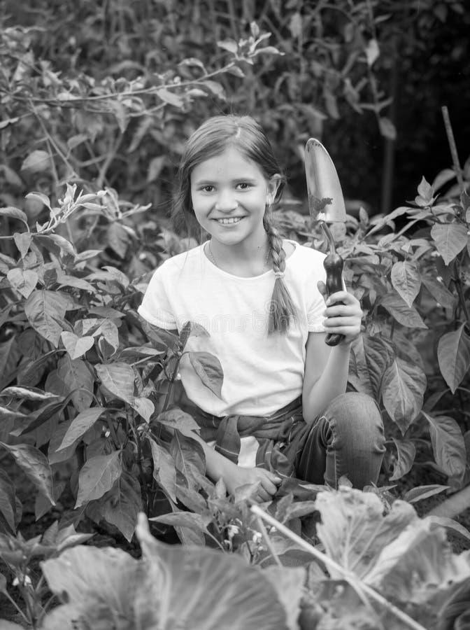 Retrato preto e branco do adolescente de sorriso que senta-se no jardim e que guarda a pá de pedreiro imagens de stock royalty free