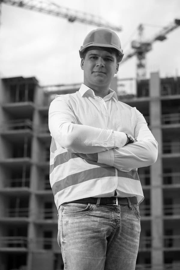 Retrato preto e branco do arquiteto em agains eretos do capacete de segurança fotografia de stock