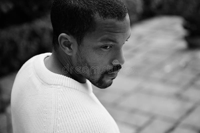Retrato preto e branco do close up do moderno afro-americano novo bonito pensativo no jérsei branco informal que anda em imagem de stock